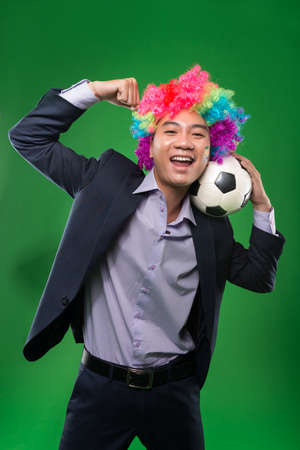 gente loca: Young Vietnamese man in a suit and a wig supporting his favorite team Foto de archivo