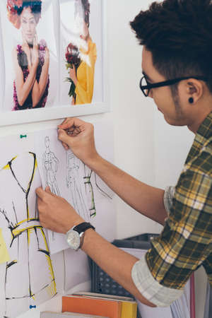 pinning: Young designer pinning fashion sketches to the wall
