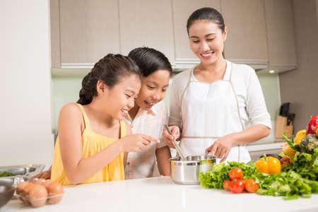 Nieuwsgierige kinderen die steelpan in handen van hun moeder onderzoeken