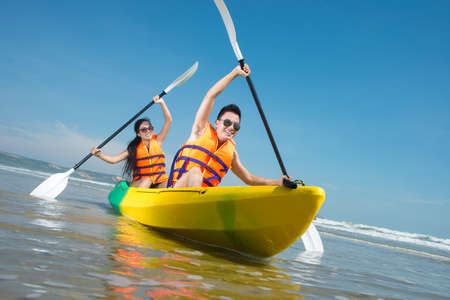 Cheerful couple paddling in kayak
