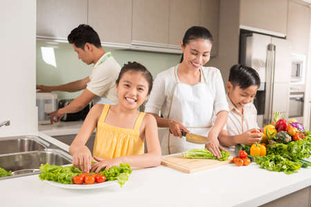 Happy Vietnamese family cooking dinner together