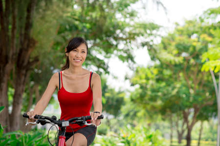 Cheerful Asian woman riding on bike in the park