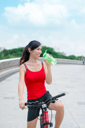 Smiling female cyclist drinking water