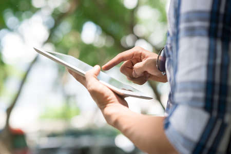 input device: Close-up image of man using digital tablet outdoors, selective focus Stock Photo
