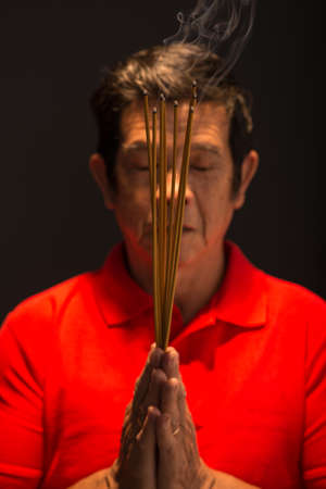 Vietnamese man praying with incense sticks in his hands