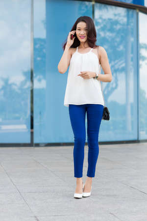 Vietnamese young woman talking on the phone outdoors
