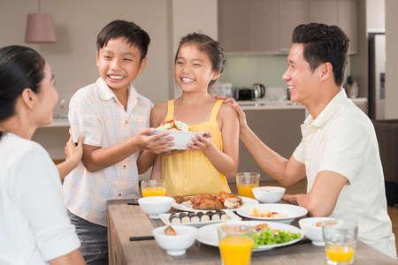 Vietnamese jongen die zijn kleine zuster helpt om de familiedinerlijst te dienen Stockfoto