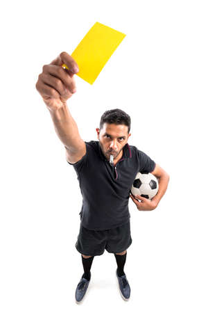 Football referee whistling and showing yellow card, view from above