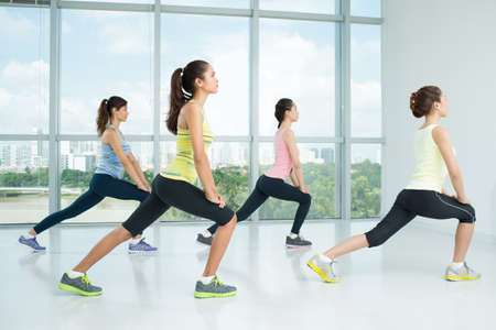 Four young girls doing lunges in the gym