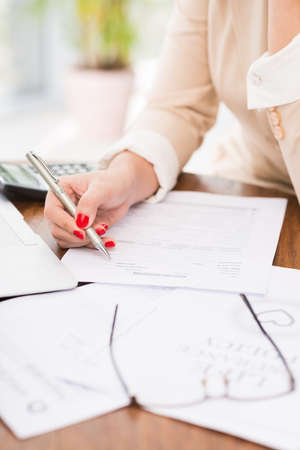 Close-up image of female accountant working with papers