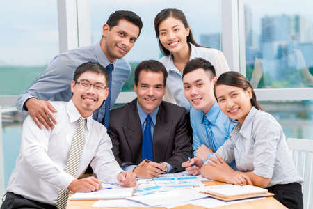 personas reunidas: Multi-ethnic business team posing grouped around Caucasian manager Foto de archivo