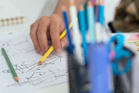 Close-up fashion designer making sketches of new collection Stock Photo