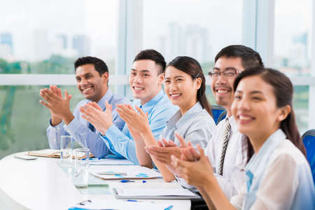 Smiling business people applauding at the conference Stock Photo