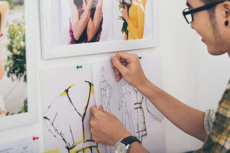 pinning: Dressmaker pinning sketches of the new collection to the wall