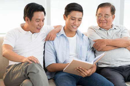 Grandfather, son, and grandson reading a book together Stock Photo