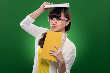 Funny Vietnamese girl holding books and looking at the camera Stock Photo