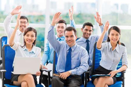 Zakenmensen op de conferentie die handen verhogen om een vraag te beantwoorden