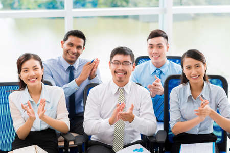 Cheerful business people applauding at the business conference