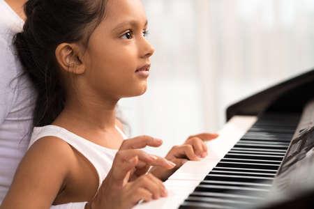 koncentrovaný: Close-up malého indického dívka hraje na klavír