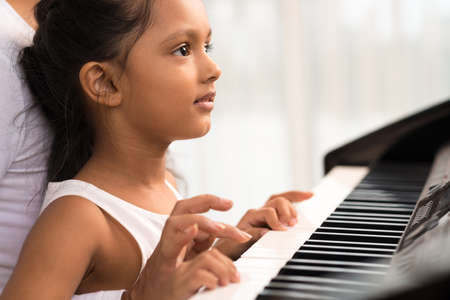 pianista: Close-up of little Indian girl playing the piano