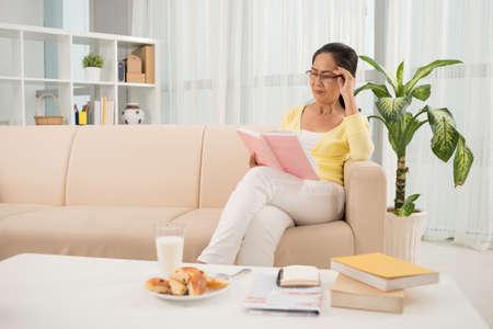 Senior Vietnamese woman in glasses reading a book Stock Photo