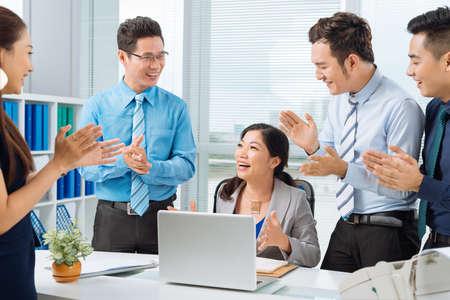 Mensen uit het bedrijfsleven applaudisseren met succesvolle vrouwelijke collega