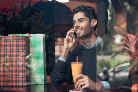 Smiling man talking on the phone and drinking juice after shopping