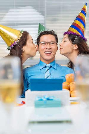 Pretty manager kissing birthday man on both cheeks