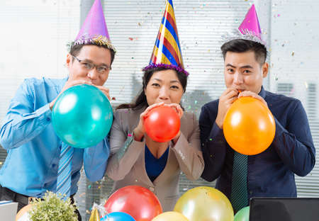 Three Asian business colleagues blowing up balloons and looking at the camera