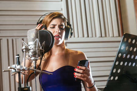 Young woman looking at the smartphone and singing a song in the recording studio