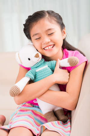 Cute Asian little girl embracing tight her favorite toy Stock Photo
