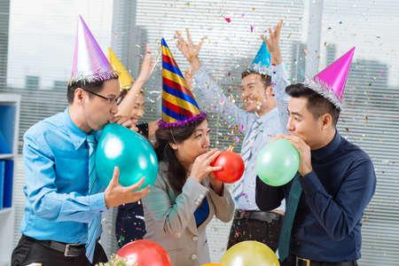 Bedrijfscollega's die ballons opblazen op de bureaupartij Stockfoto