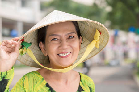 Senior Vietnamese woman in a conical hat smiling and looking at the camera