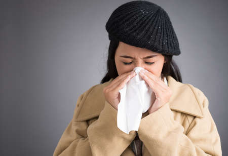 Woman in warm clothes blowing nose into tissue Stock Photo
