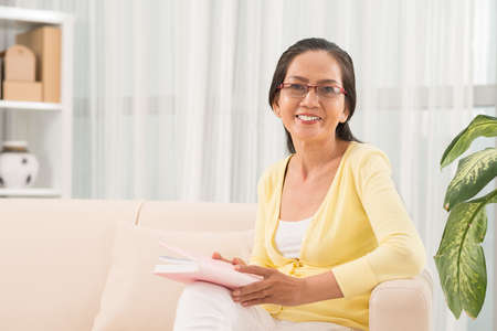 Happy senior woman reading a book at home
