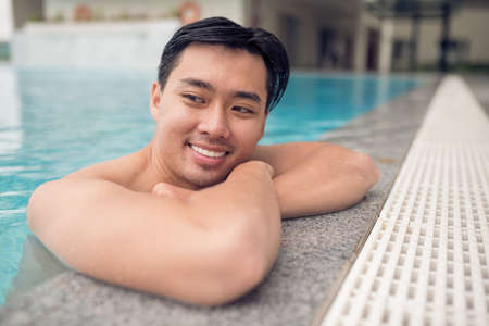 Cheerful Asian man at the edge of the swimming pool Stock Photo