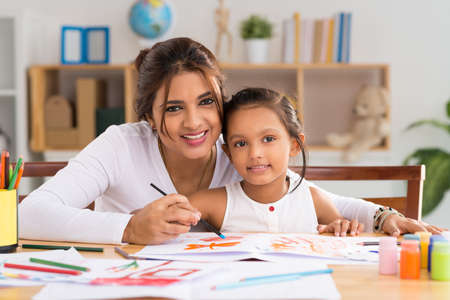 Portrait of Indian woman and her daughter painting together Stock Photo