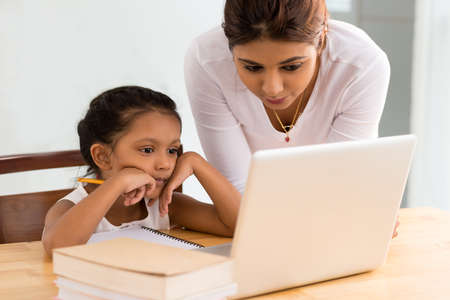 Mother explaining her daughter something on the laptop