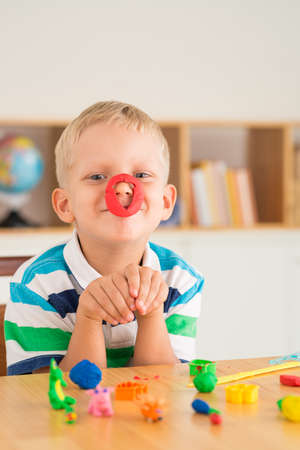 Playful boy posing with plasticine on his nose Stock Photo