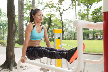 Strong Vietnamese woman performing L-sit exercise on parallel bars