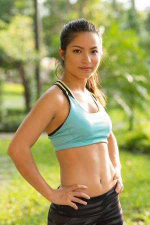 Portrait of fit Vietnamese girl wearing sports bra, her hands on hips