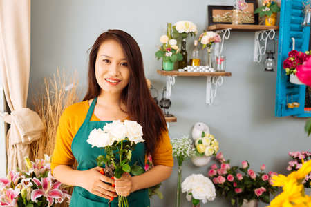Portrait of a pretty seller in her flower shop