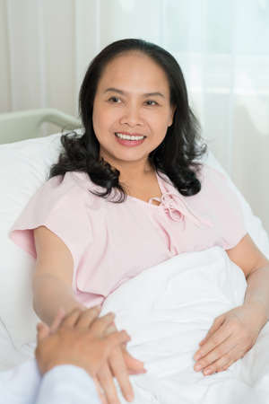 Portrait of smiling mature patient lying in bed