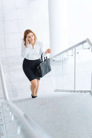 upstairs: Businesswoman talking on cell phone while walking upstairs