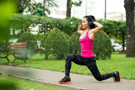 Fit Asian woman doing lunge exercise in park Stock Photo