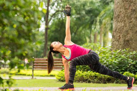Vietnamese girl exercising in park doing revolved side angle pose