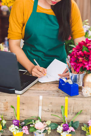 vietnamese ethnicity: Worker at cash desk writing in notepad
