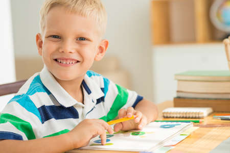 Portrait of cheerful boy drawing at the table