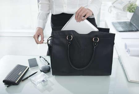 태블릿 컴퓨터를 시작하는 그녀의 핸드백에 필수적인 것들을 퍼팅 사업가 스톡 콘텐츠