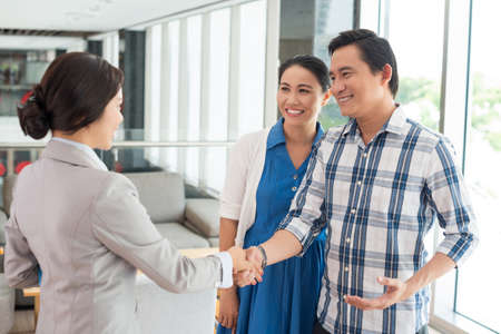 Husband shaking hands with the real estate agent Stock Photo
